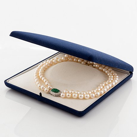 A two strand cultured pearl necklace with an 18k white gold and emerald clasp.