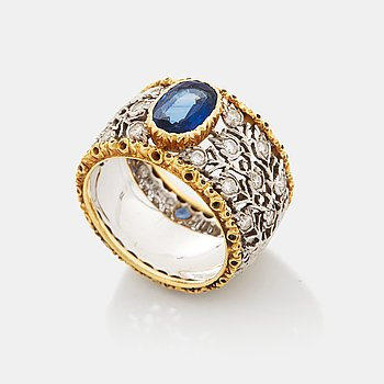 372. A Buccellati ring in 18K gold and white gold set with a faceted sapphire and round brilliant-cut diamonds.