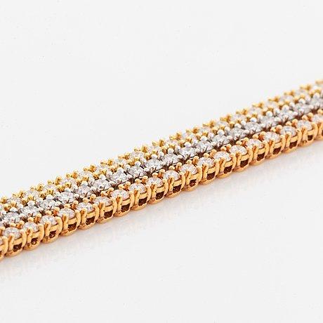 An 18k gold tennis bracelet set with round brilliant-cut diamonds.