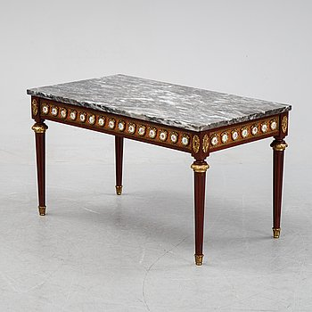 A Louis XVI style coffee table with a marble top.