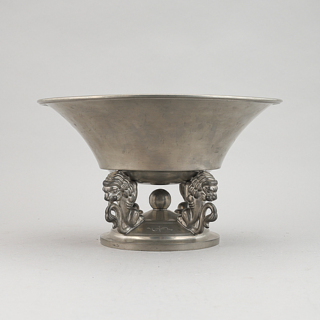 A pewter bowl held up by four lions. decorated with stylized flowers. edlunds silverfabrik ab, sweden, 1933.