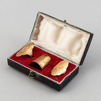 An 18K gold sew set comprising two rings and one thimble.