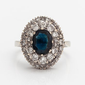 An 18K white gold ring with a sapphire and diamonds ca. 1.00 ct in total. Finland 1984.
