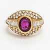 An 18k gold ring with baguette and brilliant cut diamonds and a ruby.