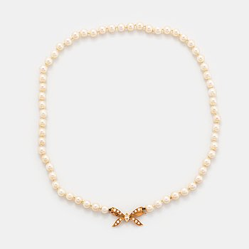 A cultured pearl necklace with a bow clasp in 18K gold set with round brilliant-cut diamonds.