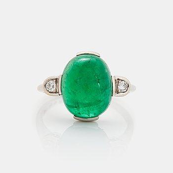 371. A platinum ring set with a cabochon-cut emerald and round brilliant-cut diamonds.