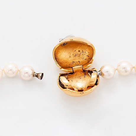 An ole lynggaard clasp in 18k gold set with a round brilliant-cut diamond.