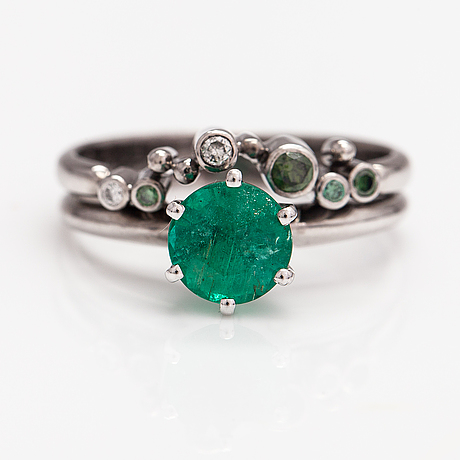 An 18k white gold ring with an emerald and green and colourless diamonds ca. 0.06 ct in total. finland 2019.