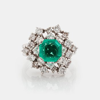 373. A platinum ring set with a faceted emerald and round brilliant-cut diamonds.