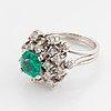 Ring platina med en fasettslipad smaragd och runda briljantslipade diamanter.
