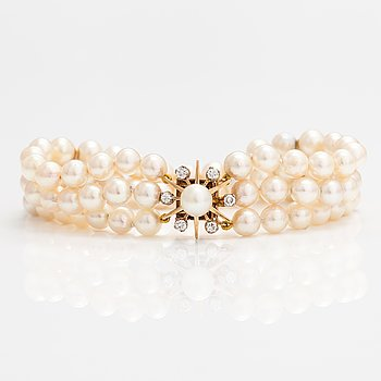 A three strand cultured pearl bracelet with 18K gold and diamond ca. 0.50 ct in total.