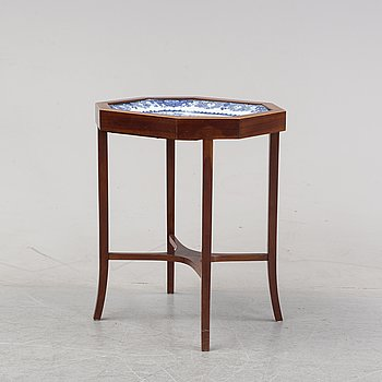 A mahogany veneered table with a Chinese blue and white porcelain charger, Qianlong (1736-95).