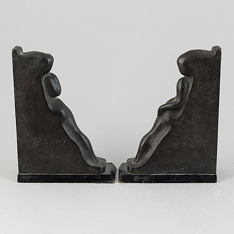 Axel gute, a pair of patinated bronze bookends, signed and dated 1919.