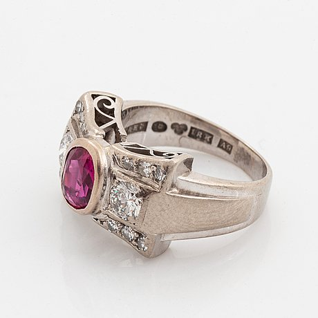 An 18k white gold ring set with a faceted ruby and round brilliant- and eight-cut diamonds.