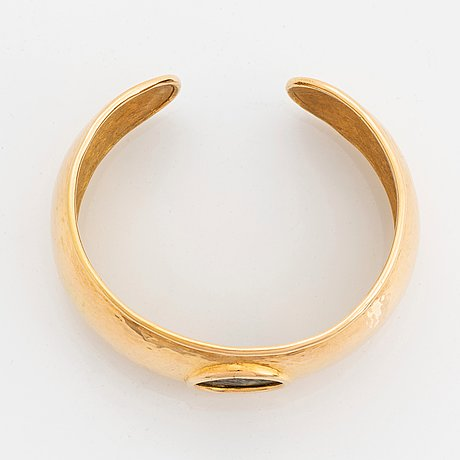 An 18k gold bangle set with an ancient coin.