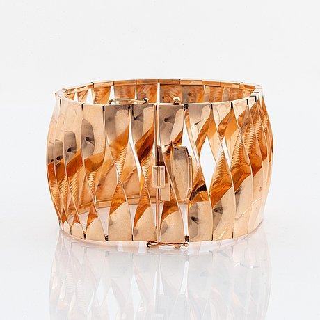 A 14k gold bracelet and a brooch.