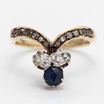 A 14K gold ring with a synthetic sapphire, radiant-cut diamonds ca. 0.28 ct in total and rose cut diamonds.