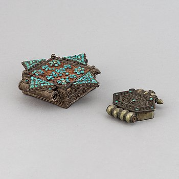 Two metal pendants with turkoise inlay, Tibet, circa 1900.