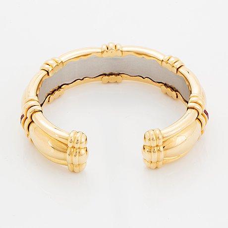 An 18k gold bracelet set with step-cut rubies.