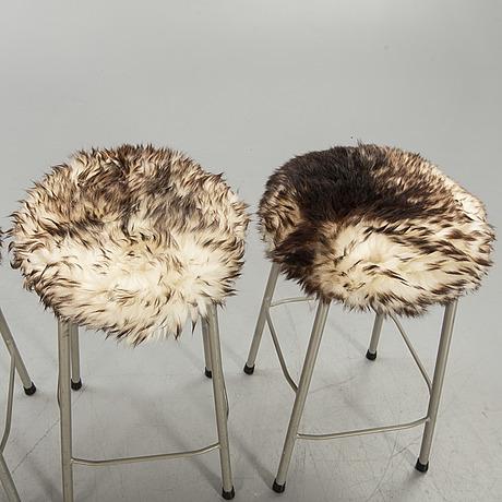 A set of four modern stolls with sheepskin.