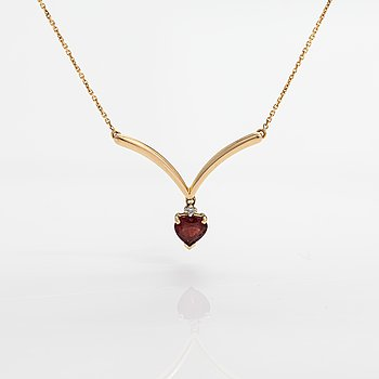 A 14K gold necklace with a garnet and a diamond ca. 0.009 ct.