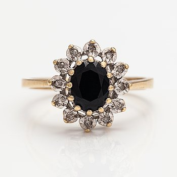 A 14K gold ring with a sapphire and diamonds ca. 0.08 ct in total. UK.