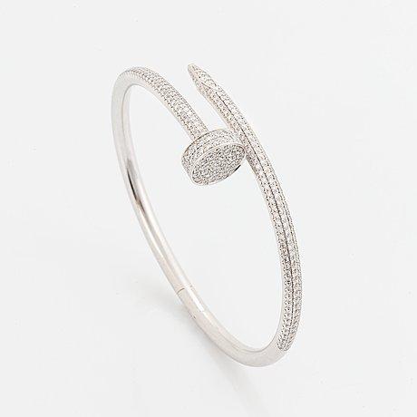 """A cartier """"juste en clou"""" bracelet in 18k white gold set with round brilliant-cut diamonds."""