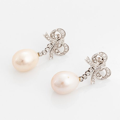 A pair of 18k gold and cultured pearl earrings set with round brilliant-cut diamonds.