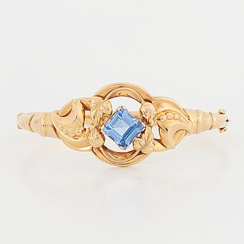 An 18K gold bangle set with a blue synthetic stone.