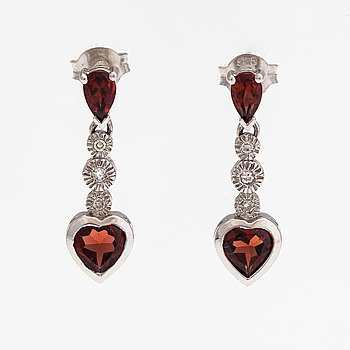 A pair of 14K white gold earrings with garnets and diamonds ca. 0.10 ct in total.