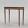A louis xvi style console table with a marble top.