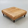 A leather ottoman/coffee table alter part of the 20th century.