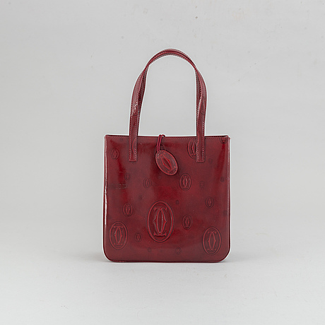 Cartier, a burgundy patent leather handbag and wallet.