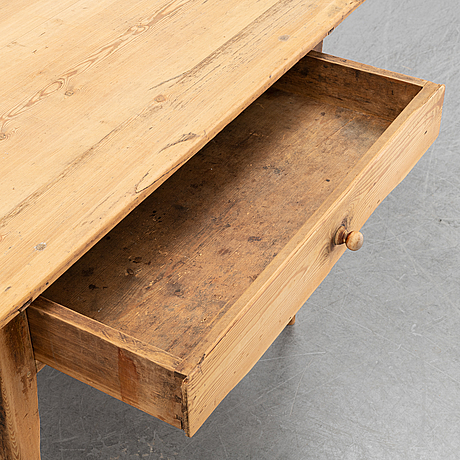 An early 19th century pine table with a drawer.