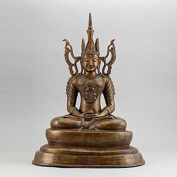 A seated buddha, yellow metal, possibly Nepal, 20th century.