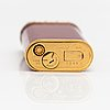 Cartier, a gilded and laquered metal lighter. marked cartier, paris, 06311 v, swiss made.