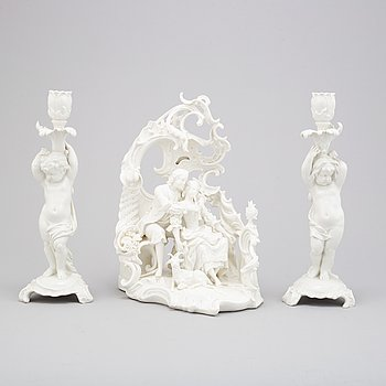 A German white glazed figure group and a pair of Berlin candle sticks, 20th Century.