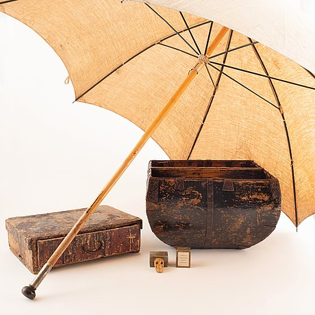 A mixed lot comprising a wooden firewood basket, a box, a sun parasoll, and two small resin scull sculptures.