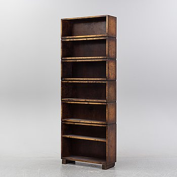 A stained birch shelving system, first half of the 20th Century.