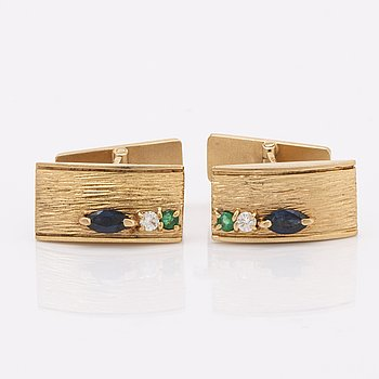 Cufflinks 18k gold with sapphires, emeralds and brilliant-cut diamonds, total weight 15,9 g, approx 2 x 1 cm.