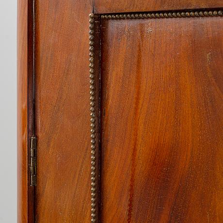 A mahogany veneered empire cupboard, first half of the 19th century.