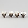 A set of four ottoman parcel-gilt silver xarfs with russian kuznetzov porcelain cups, around the year 1900.