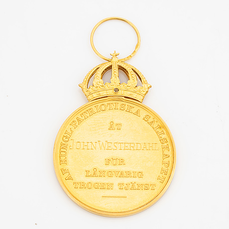 A 18k gold medal with ribbon.