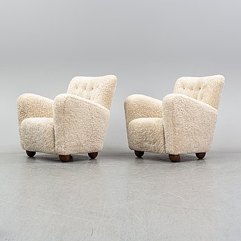 A pair of 1940's lounge chair with later sheepskin upholstery.