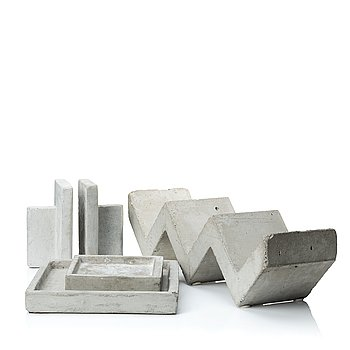 A mixed lot comprising a pair of limestone bookends, a bookshelf and two plates in concrete.
