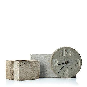 Stina Lindholm, a contemporary concrete planter 'Spira', a concrete flower pot and a wall clock.