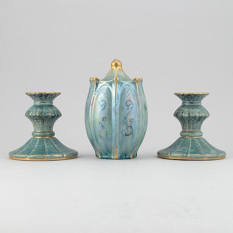 Josef ekberg, a pair of creamware lustre candlesticks and a lided vase, gustavsberg, 1927-1930.