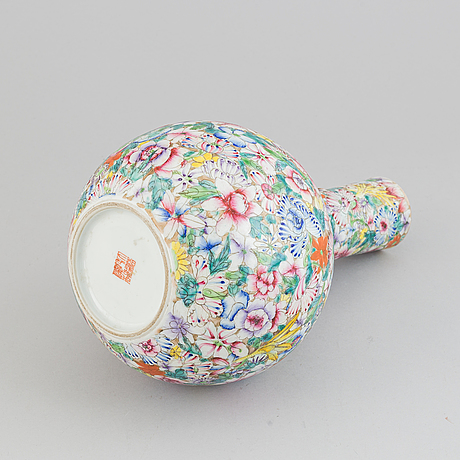 A chinese globular shaped vase, richly decorated with flowers and a dragon and a bat, second half of the 20th century.