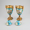 A pair of pordelain and gilt brass urns in teh style of sevres, 20th century.