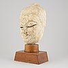 A south east asian stone mass sculpture of a head, presumably modern manufacturing.
